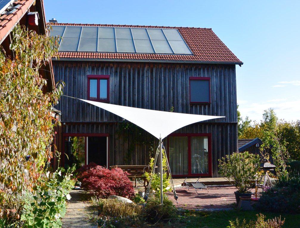 Dreipunkt Sonnensegel in der Farbe flanell an einem Holzhaus. Unsere Sonnensegel passen zu jedem Haus und werten die Umgebung und Ihr Haus auf.