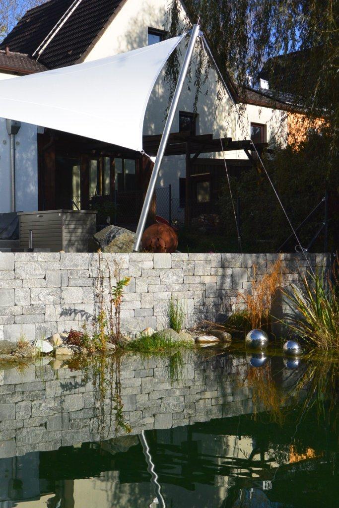 Design in Perfektion, Spiegelung des Segels im Teich, stilvolle und professionelle Terrassenüberdachung